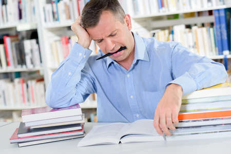 Frowning man reading with pen in mouth Stock Photo