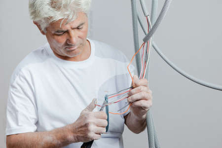 electric power: Electrician clipping electrical wires Stock Photo