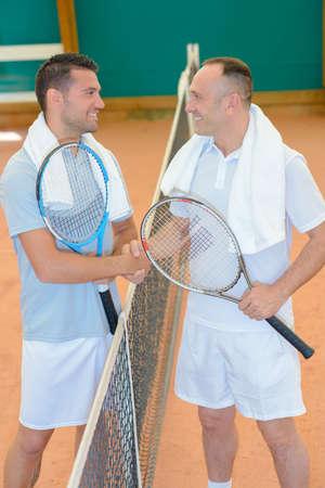 Men shaking hands over tennis court net Stock Photo