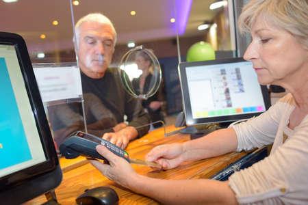 Klant krijgt geld uit bank kassier Stockfoto