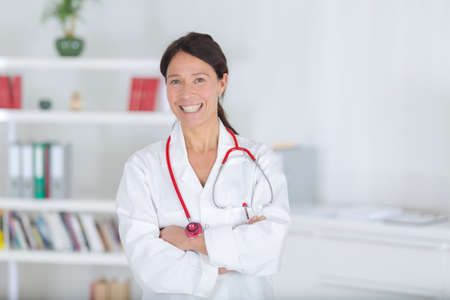 smiling young doctor standing with arms folded