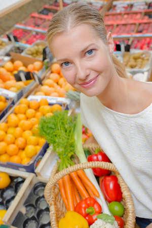 Lady holding wicker basket of vegetables, in supermarket