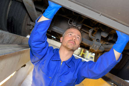 qualified worker: mechanic working in the garage