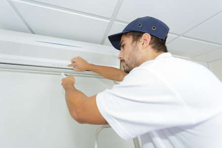 ac: technician checking ac installation in clients building