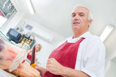butchering: Upward view of butcher holding knife