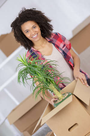 beautiful woman with carton boxes moving in her new house Stock Photo
