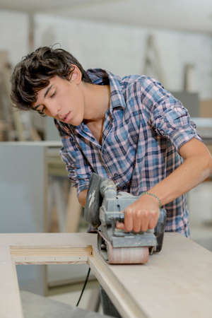 Young carpenter using a belt sander