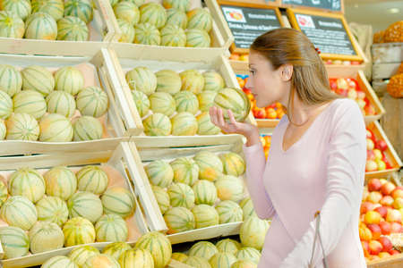 grocers: Lady smelling melon in grocers