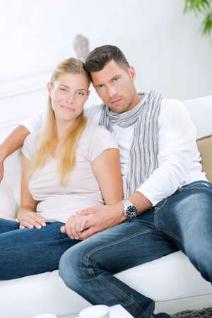 Couple sat on couch holding hands