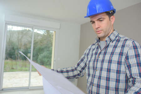 Man in house looking at plans Stock Photo