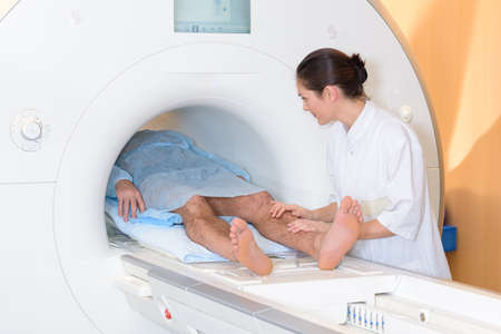 claustrophobic: Nurse holding legs of patient in scanner