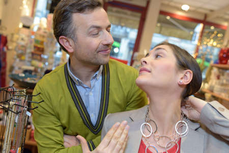 attaching: man attaching necklace to girls neck in retail store