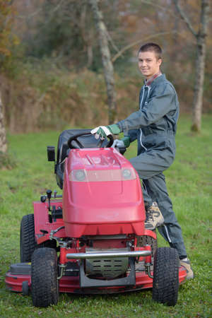 stepping: Young man stepping on to mower