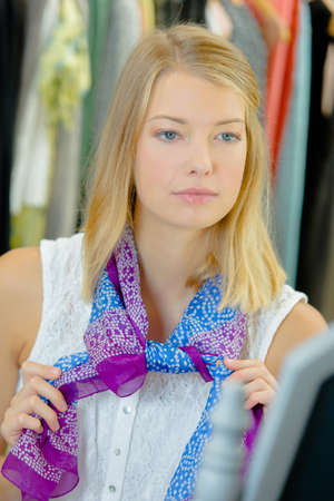 colourful tie: Lady in shop tying  a scarf