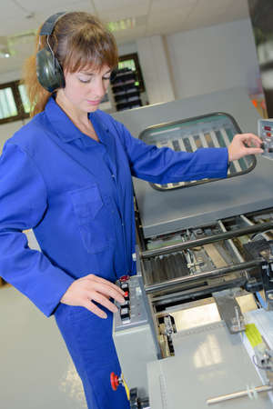 mechanician: Female worker setting up industrial machine