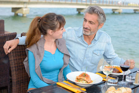 Couple dining outside in riverside restaurant Stock Photo