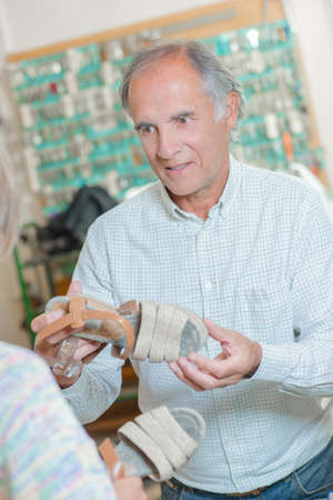 peer to peer: Cobbler discussing sandals with customer Stock Photo