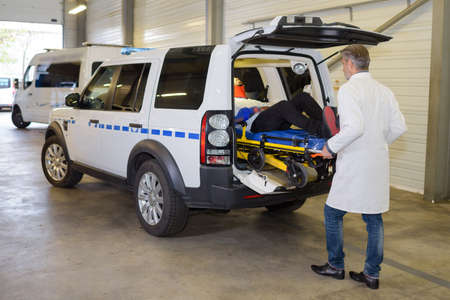responce: Paramedic loading stretcher into ambulance vehicle Stock Photo