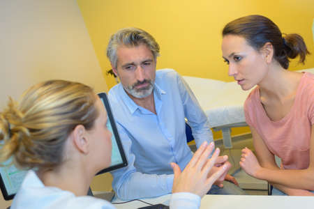 insist: Doctor talking seriously to middle aged couple