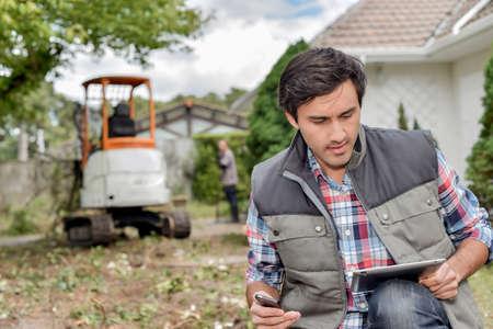paysagiste: Man extérieur en utilisant la tablette, pelle en arrière-plan