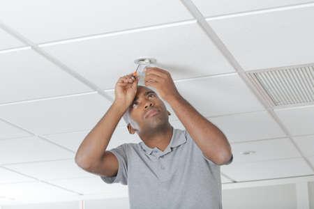 Man replacing bulb in spotlight Stock Photo