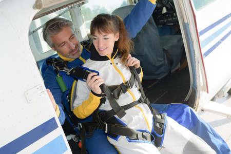 thrill: Man and woman preparing for parachute jump