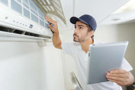 technicians: young contractor working carefully and seriously at clients office
