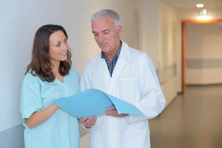 advise: nurse and doctor in hospital corridor