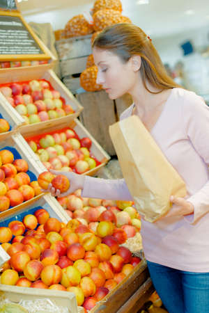 Putting fruit into a paper bag at the supermarket Stock Photo