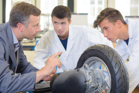 pressurized: Mechanic with wheel teaching apprentices