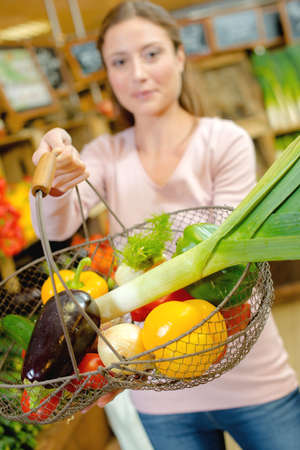 Lady holding forward a wire basket of fruit and vegetables