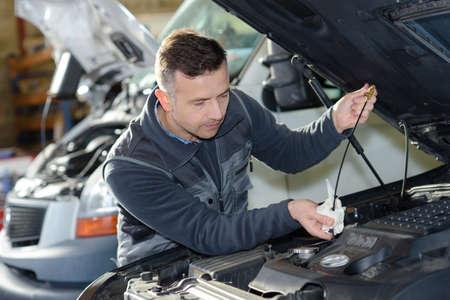 Auto monteur ter vervanging van olie op de motor in de garage Stockfoto - 72852536