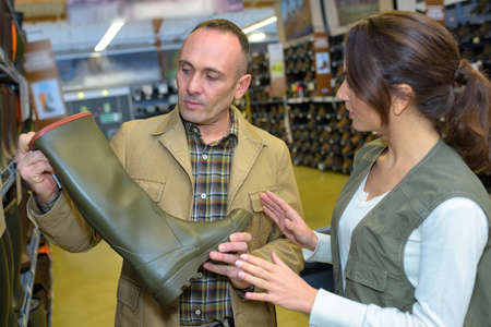 welly: Man looking at wellington boot in store