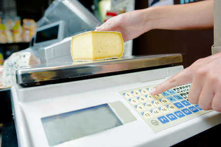 grams: Weighing cheese on electronic scales Stock Photo