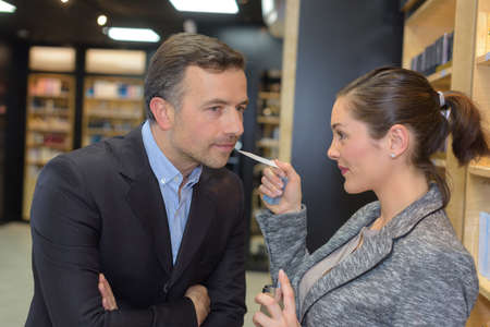 inhaled: beautiful saleswoman showing beauty products to male customer