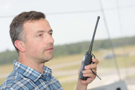 Profile of man using walkie talkie
