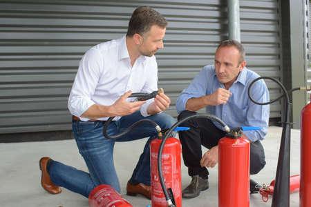 Mannen die brandblussers onderzoeken