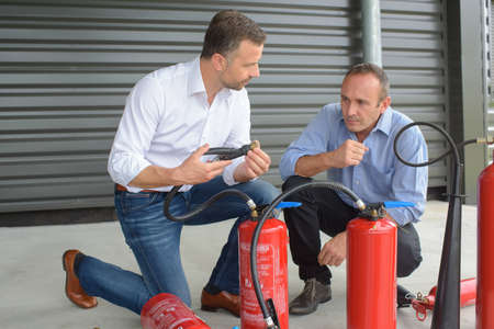 Men examining fire extinguishers Stock Photo - 72857423
