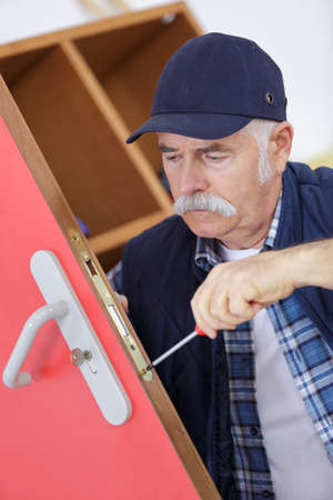 jobbing: senior professional with different types of keys in locksmith