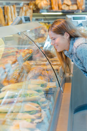 woman looking at bread counter