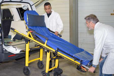 medical career: Men loading stretcher into ambulance