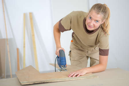 blonde females: Lady using electric jigsaw
