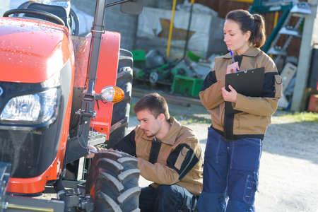 mechanician: mechanicians examining tractors engine