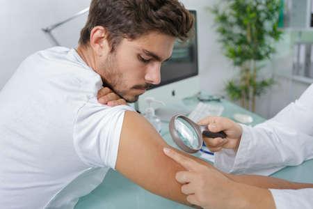 close-up of doctors hands checking mans moles Standard-Bild