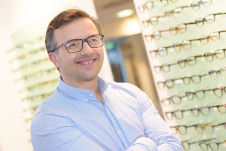 attempt: portrait of handsome mature man trying new glasses at optician Stock Photo