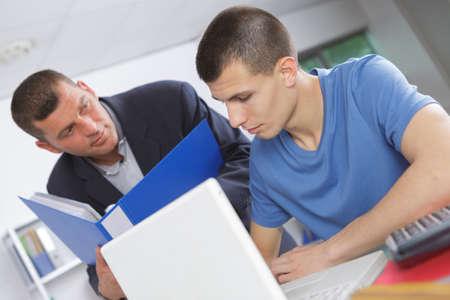 coursework: Teacher helping young man using laptop