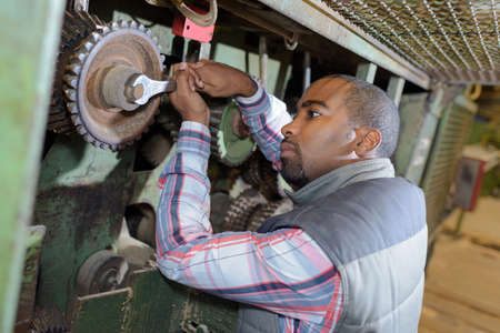 man nuts: Worker tightening nut with spanner