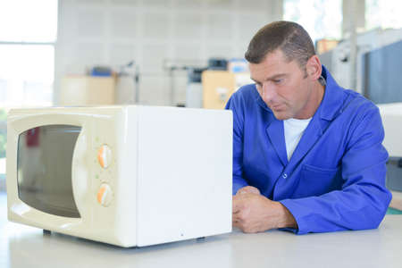 Man working on microwave oven