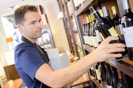 Worker stacking wine on to shelf