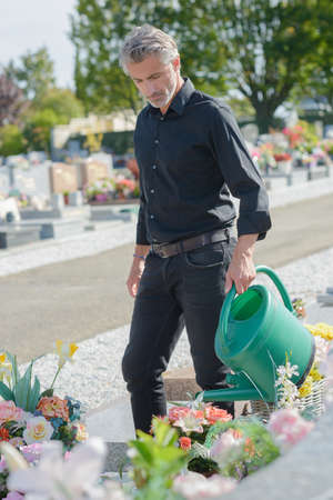 groundskeeper: watering a grave